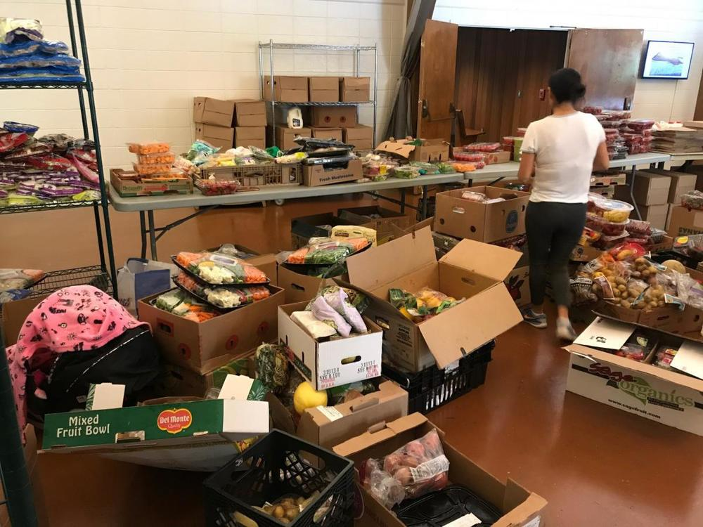 A volunteer at Malachi's Storehouse arranges produce for the 150 people who visit each Wednesday to get groceries.