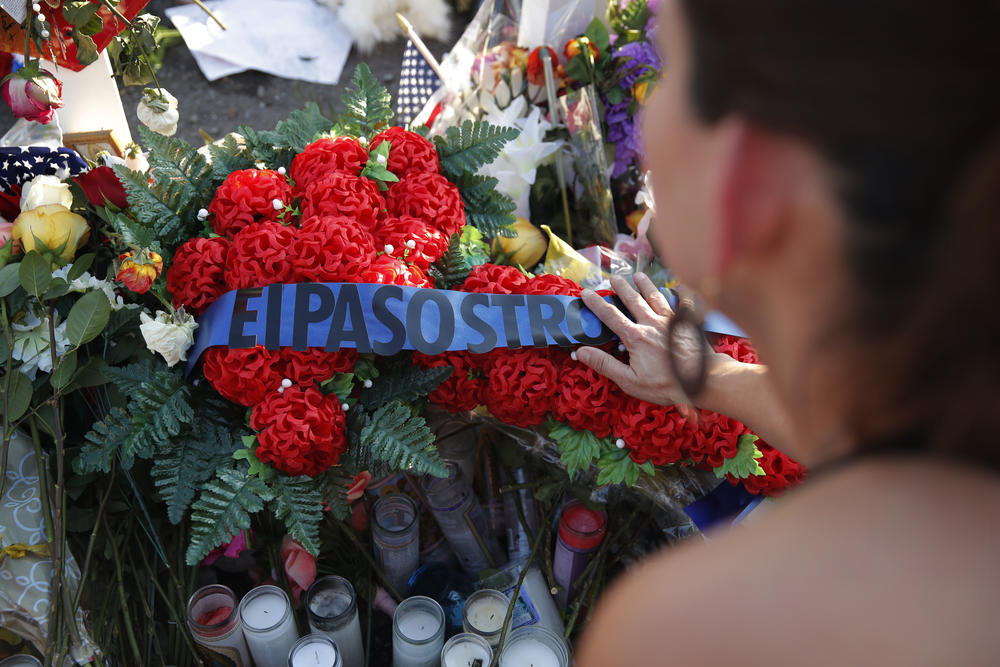 A woman leaves flowers at a makeshift memorial at the scene of a mass shooting at a shopping complex Tuesday, Aug. 6, 2019, in El Paso, Texas.