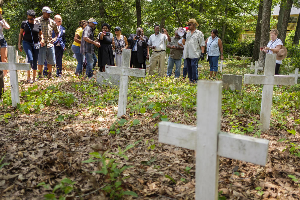 Tyrone Brooks leads a tour through a cemetery of anonymous graves surrounded by an office park to a marker for 1946 lynching victim Mae Murray Dorsey.