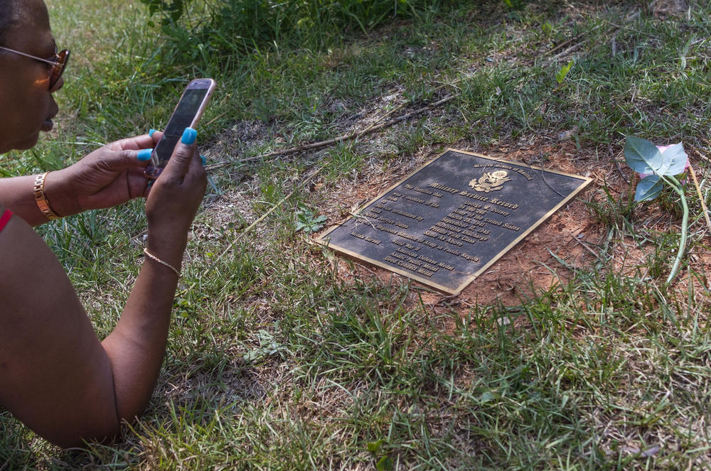 Hope Dorsey makes a photo of a marker commemorating the service during World War Two of her relative George Dorsey. George Dorsey was one of four people killed by a lynch mob at Moore's Ford Bridge in Walton County in 1946.