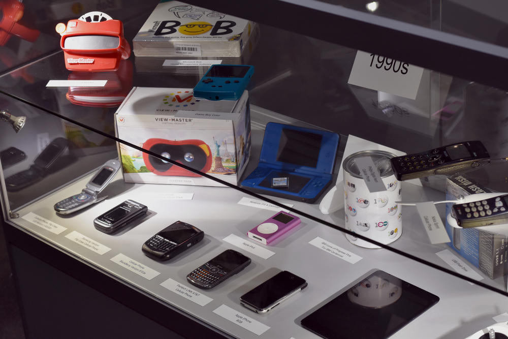A display case holds several technological artifacts from the 1990s and 2000s, including the first iPhone model and a BlackBerry.