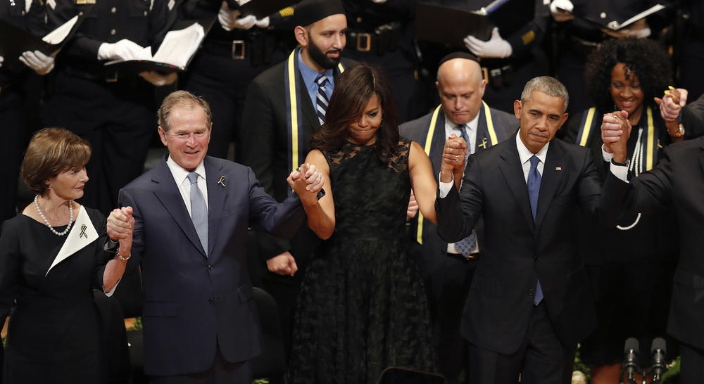 From left, former first lady Laura Bush, former President George W. Bush, first lady Michelle Obama and President Barack Obama join hands during a memorial service with the families of the fallen Dallas police officers.