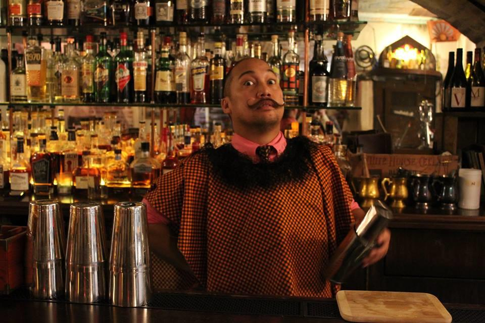 A costumed bartender mixes a drink at the American Prohibition Museum bar.