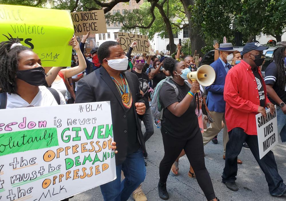Savannah organizers Faith Harris (left) and Nychorida Austin (with bullhorn) lead a protest march flanked by New Georgia Project chairman Francys Johnson, Savannah Mayor Van Johnson (right, in red) and former Mayor Otis Johnson (right, in blue).