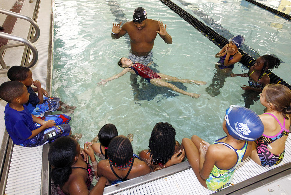 USA Swimming, Olympic Gold Medalist Cullen Jones, center, gives area children a swimming lesson at Centenary College in Shreveport La.