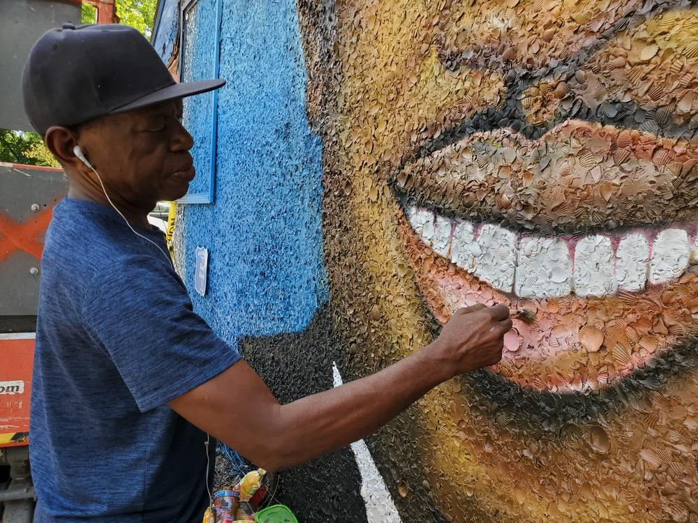 Artist Marvin Weeks paints a mural of Ahmaud Arbery on the side of the future Brunswick African American Cultural Center.