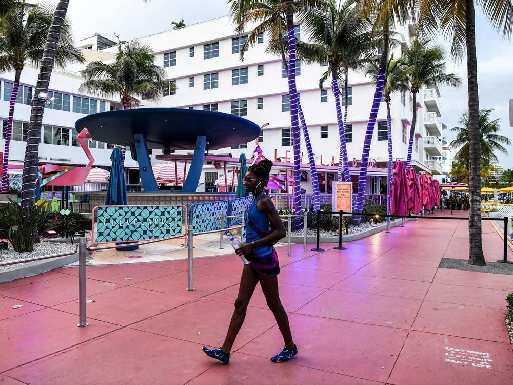 A woman walks past a closed restaurant this week in Miami Beach, Fla., during the coronavirus pandemic.