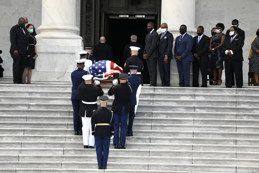 Family members watch as the American flag-draped casket of the late Rep. John Lewis, D-Ga., is carried by a joint services military honor guard outside the U.S. Capitol before a ceremony Monday in Washington, D.C.