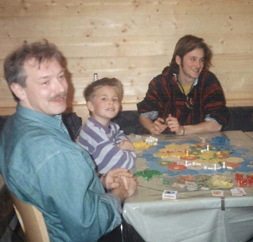 A Teuber family photo from 1994 shows Klaus (left), Benjamin and Guido Teuber playing a test version of the Catan game. Catan creator Klaus Teuber says the family still plays together but admits he usually loses.