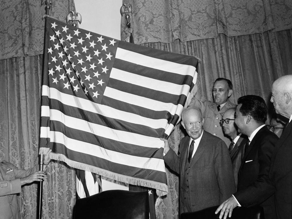 President Dwight Eisenhower helps unfurl the new 50-star flag on Aug. 21, 1959 after signing a proclamation making Hawaii the 50th state of the union. At right is Daniel K. Inouye, Democratic congressman-elect from Hawaii.
