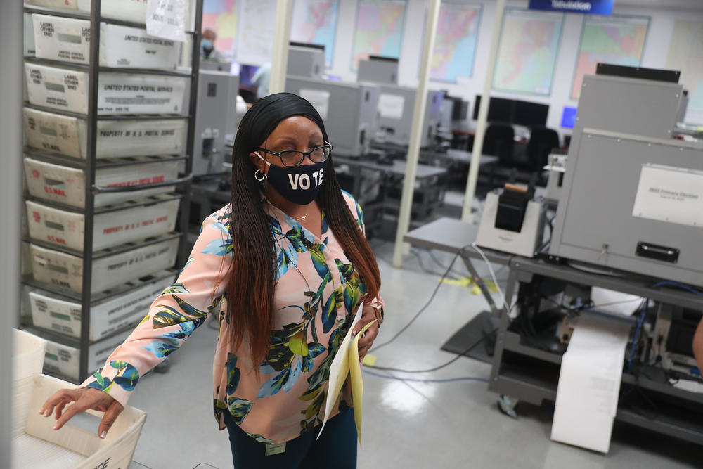 Workers at the Miami-Dade County Elections Department work on tabulating mail-in ballots Tuesday in Doral, Fla.