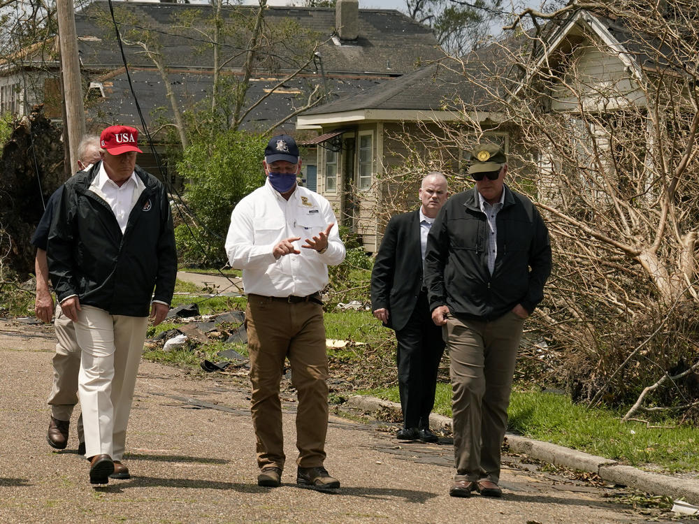President Trump listens to Louisiana Gov. John Bel Edwards, center, as he tours damage from Hurricane Laura, in Lake Charles, La.