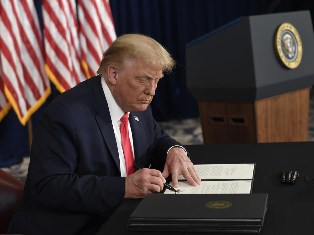 President Trump signs one of four executive orders addressing the economic fallout from the pandemic in Bedminster, N.J., on Aug. 8. The Trump administration has given employers the option to stop collecting payroll taxes, but workers may have to repay the money next year.
