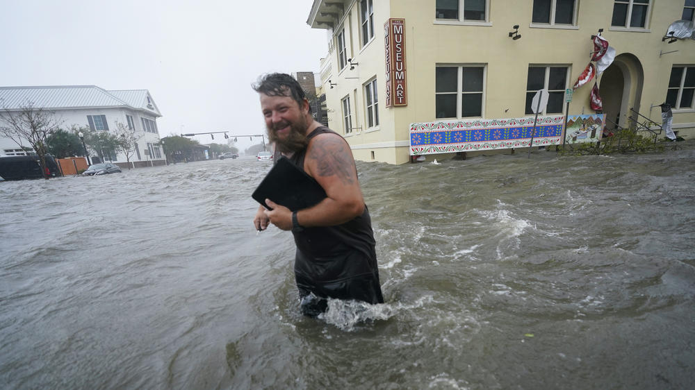 Trent Airhart wades through floodwaters after retrieving items from his vehicle in downtown Pensacola, Fla., Wednesday. Hurricane Sally is causing flooding across a wide area of the northern Gulf Coast.