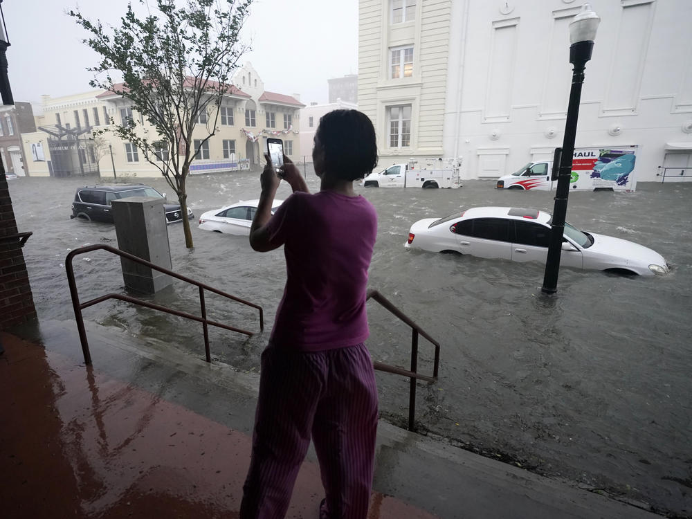 Floodwaters swamp cars on a street in downtown Pensacola, Fla., Wednesday. Hurricane Sally made landfall near Gulf Shores, Ala., as a Category 2 storm, pushing a surge of ocean water and dumping torrential rainfall.