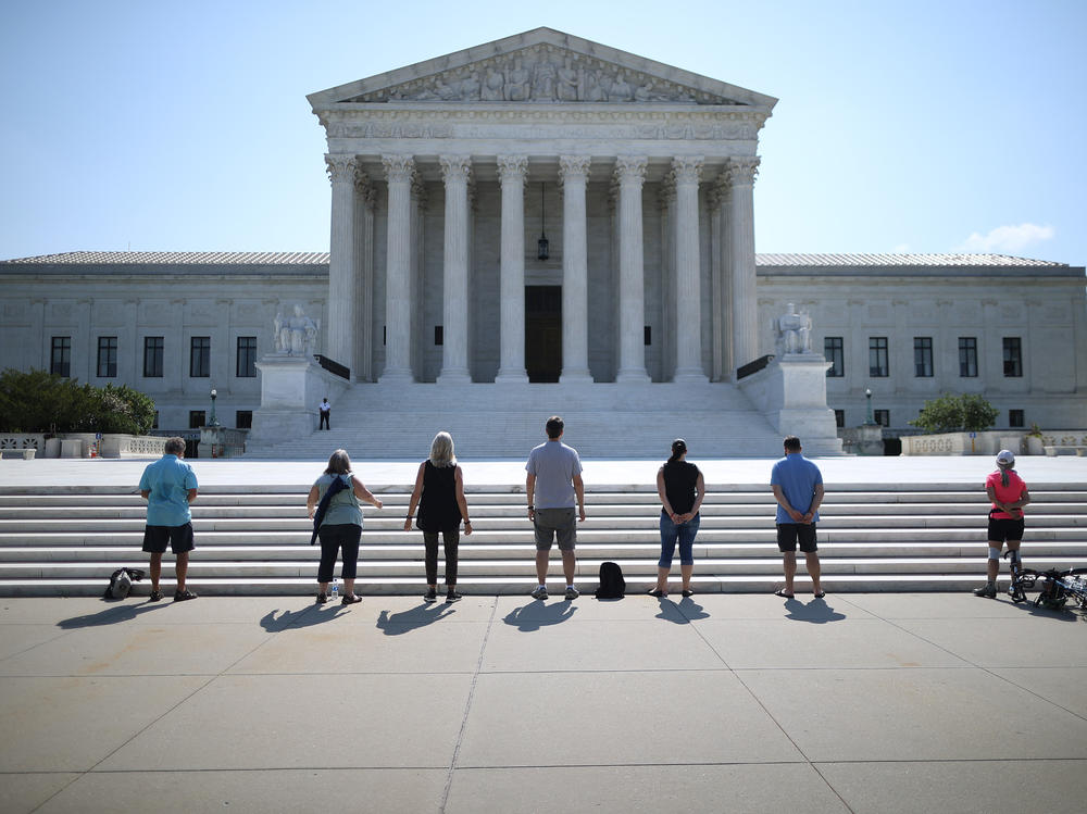 Demonstrators pray in front of the U.S. Supreme Court on July 8, a day the court ruled that employers with religious objections can decline to provide contraception coverage under the Affordable Care Act. With the death of Ruth Bader Ginsburg, the ACA's future is in doubt.