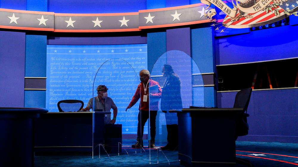 Workers install plexiglass protections on the stage of the debate hall ahead of the vice presidential debate Salt Lake City.