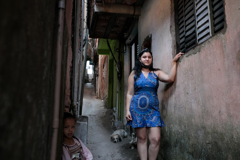 Jessica Fernandes de Andrade  outside her house in a favela in São Paulo, Brazil. She contracted the novel coronavirus and has recovered but still suffers from fatigue, which has kept her from working.