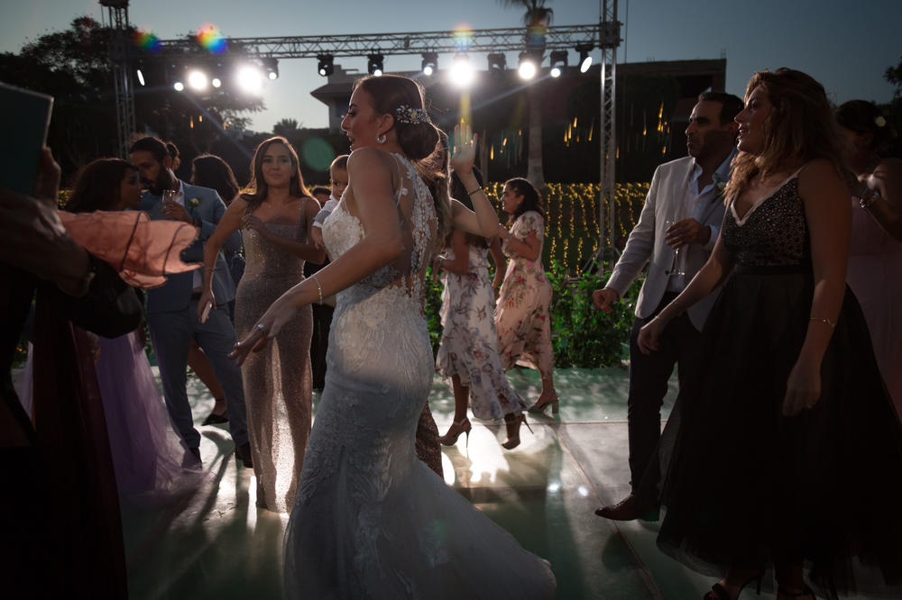 Dina el-Harazy, center, dances at her wedding reception in Cairo. The wedding was rescheduled three times because of coronavirus restrictions.