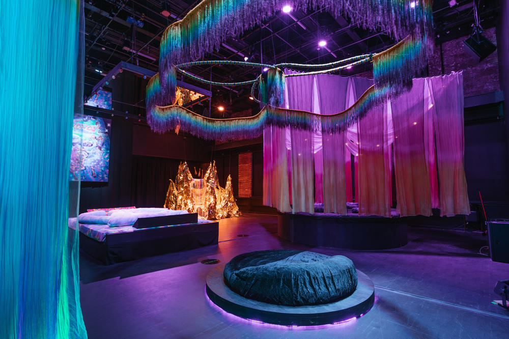 <em>Back Power Naps,</em> 2019, is an elaborate arrangement of plush beds and bean bags in a spacious, black box theater by interdisciplinary artist Navild Acosta.