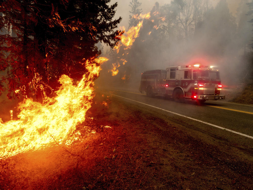 A firetruck drives along state Highway 168 last month while battling the Creek Fire in the Shaver Lake community of Fresno County, Calif.