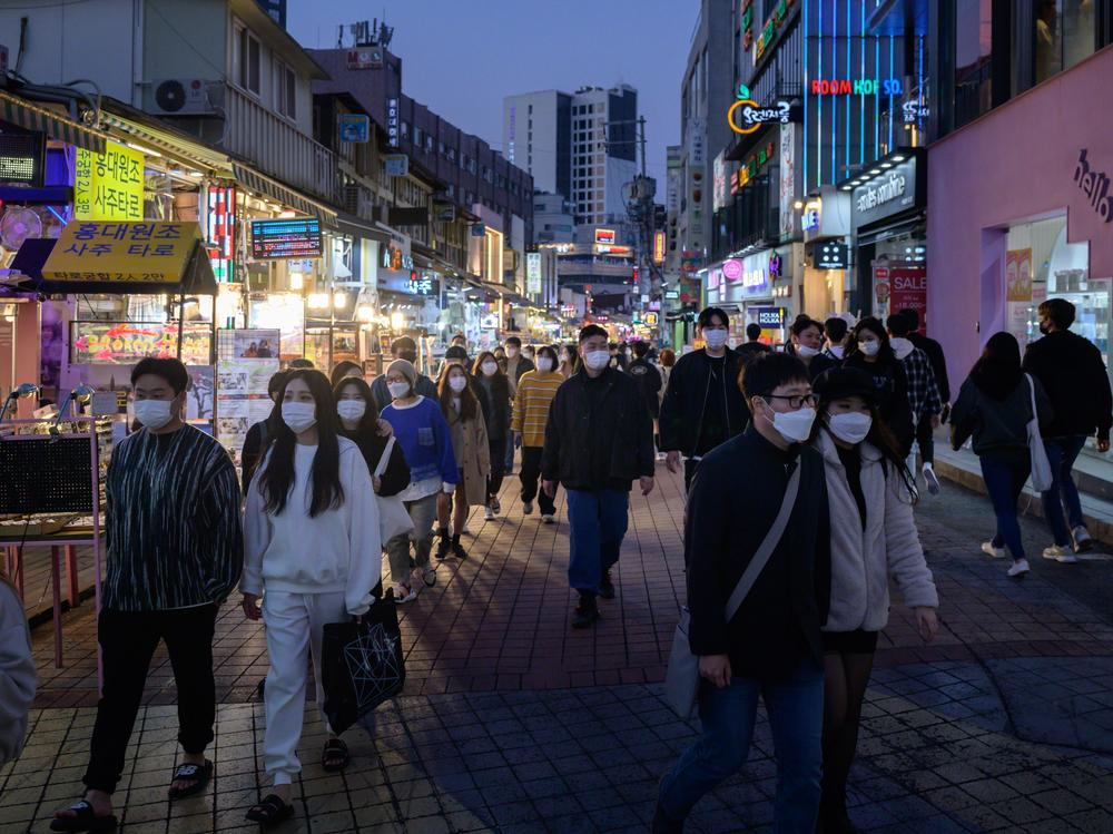 People wearing face masks walk on a street Sunday in the Hongdae district of Seoul, South Korea.