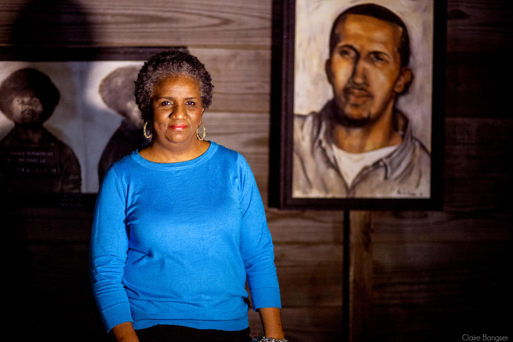 Mac's mother, Sheila Phipps, stands with a portrait she painted of her son, part of a series called Painted Justice, depicting prisoners who were wrongfully or harshly accused.