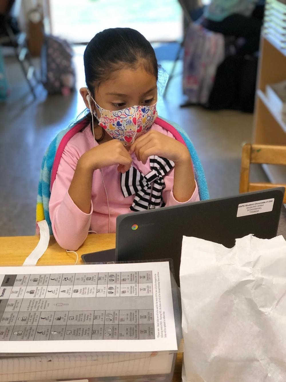 Angelique, a third grader, follows her afternoon virtual classes on an iPad at the Ann Arbor Community Learning Center, A learning hub helping the children of undocumented families attend to their virtual classes while their parents go to work.