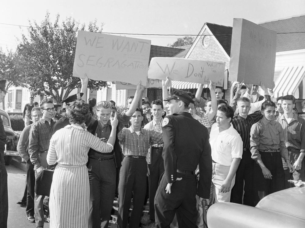 With signs calling for segregation, a crowd gathers outside the William Frantz Elementary School in New Orleans on Monday, Nov. 14, 1960, the first day of classes for 6-year-old Black student Ruby Bridges.