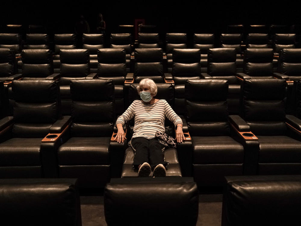 A woman sits in a theater in Irvine, Calif., waiting for a movie to start, on Sept. 8. A COVID-19 vaccine could unleash pent-up spending from households that have mostly avoided activities like going to the gym during the coronavirus pandemic.