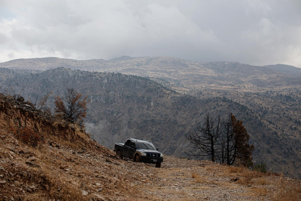 A pick-up truck that's been modified to be used for fighting wildfires is parked amid cedar and juniper trees that were burned in a recent wildfire, in the Mishmish forest.