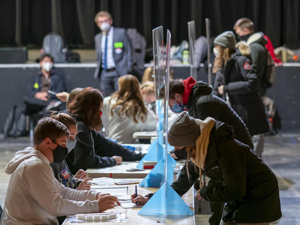 Poll workers check voters' identifications on Election Day at the Orpheum Theater in Madison, Wis. The Trump campaign has announced it is filing for a recount in two Wisconsin counties.
