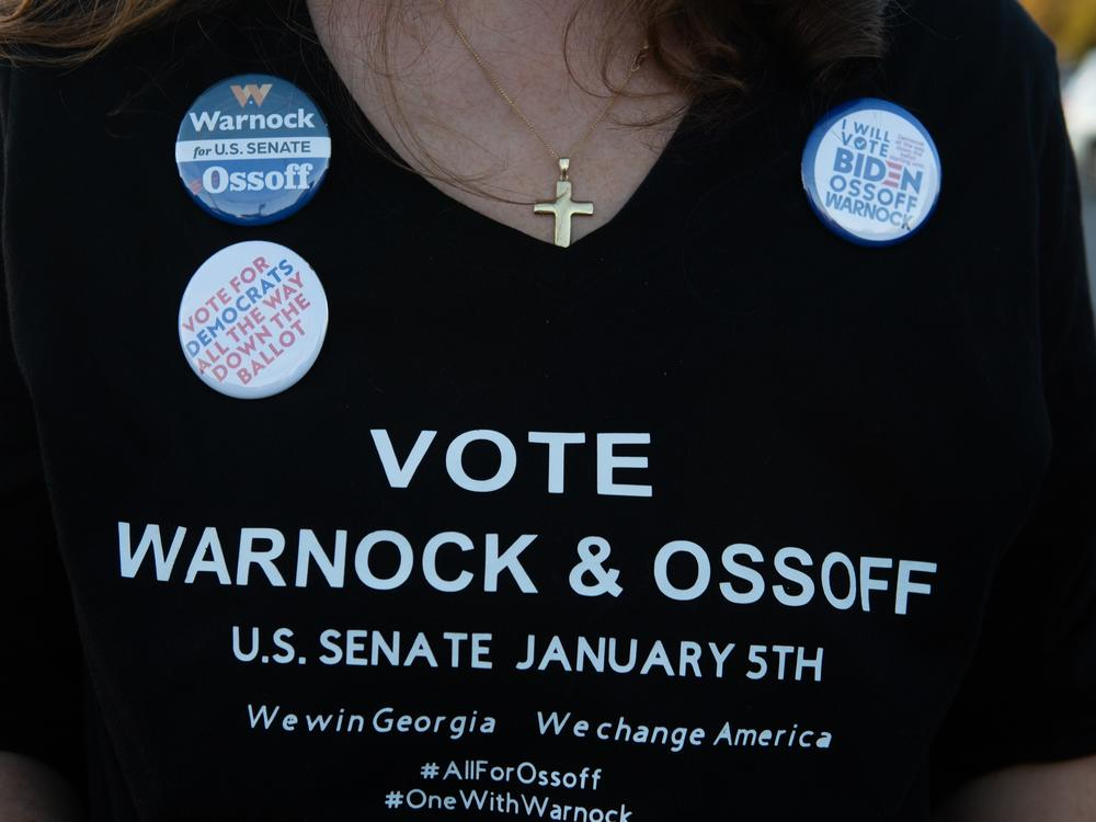 A supporter wears a homemade T-shirt to promote Democratic U.S. Senate candidates Jon Ossoff and Raphael Warnock of Georgia during a rally on Nov.15, in Marietta, Ga.