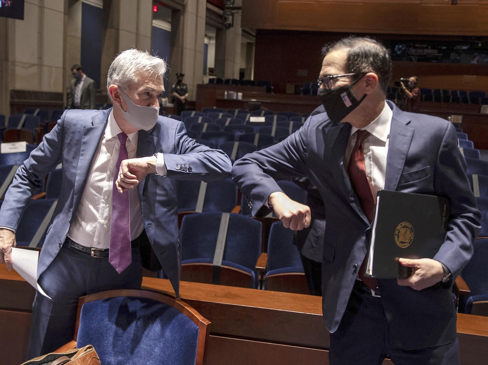 Federal Reserve Chairman Jerome Powell, left, and Treasury Secretary Steven Mnuchin bump elbows after concluding their testimony before Congress on June 30. The Fed and Treasury engaged in a rare clash over the fate of key pandemic lending programs.