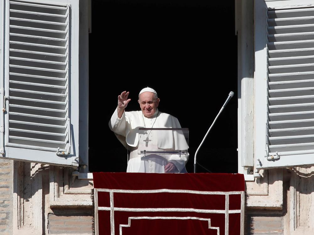 Pope Francis arrives at the window of his studio for the Angelus noon prayer in St. Peter's Square at the Vatican, Sunday.