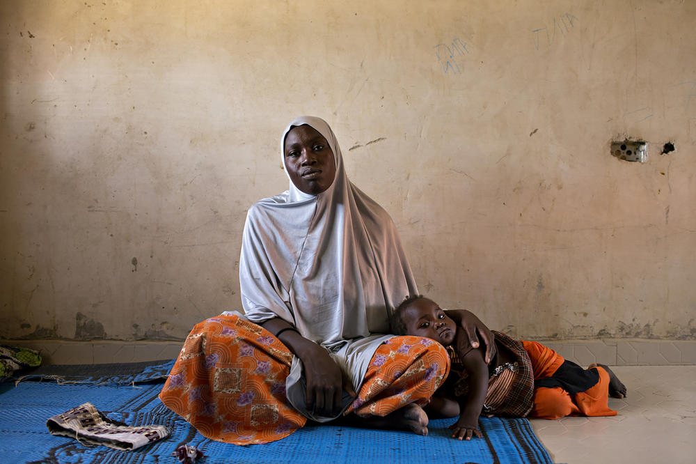 Halima Ibrahim, 30, with her daughter. After her village was attacked, Ibrahim was forced to live under Boko Haram rule for nine months in Monguno, Nigeria, where insurgents would threaten to kill people in front of them as intimidation. After the military rescued people in captivity, she reunited with her husband in Maiduguri, where she lives in a refugee camp with him and their children.
