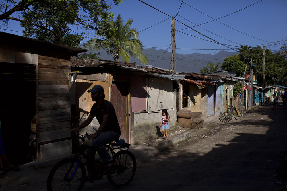 A young girl walks along the streets of a neighborhood in San Pedro Sula, Honduras, which has some of the highest homicide rates in the world due to violence from gangs and police.