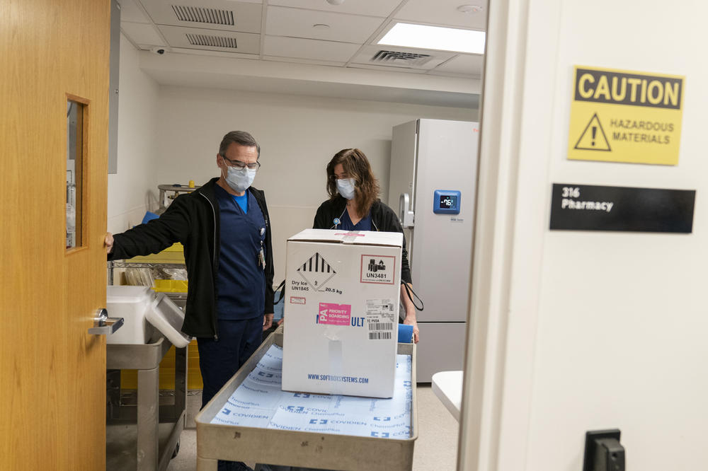 Pharmacists Richard Emery and Karen Nolan wheel a box containing the Pfizer-BioNTech COVID-19 vaccine next to a storage freezer as it arrives at Rhode Island Hospital in Providence, R.I, on Monday.