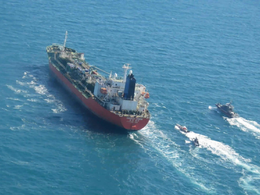 A seized South Korean-flagged tanker is escorted by Iranian Revolutionary Guard boats in the Persian Gulf. This comes as Tehran is enriching nuclear fuel to 20% purity.