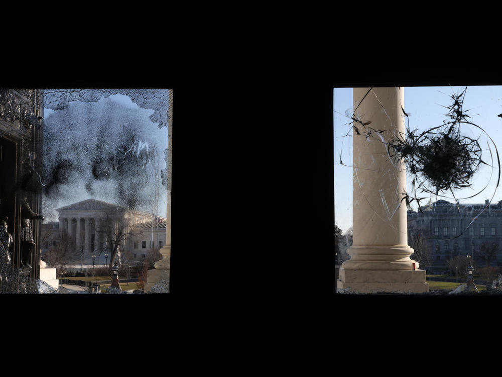 The U.S. Supreme Court is seen through a broken window at an entrance of the U.S. Capitol Wednesday.