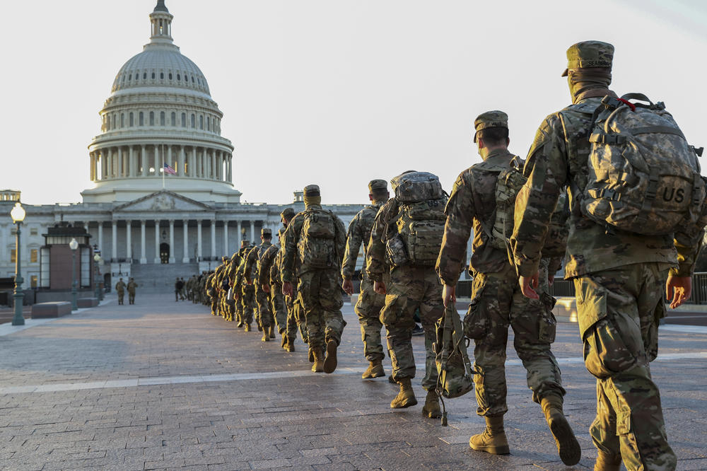 Members of the National Guard arrive at the U.S. Capitol this week to assist with security ahead of President-elect Joe Biden's inauguration. A new poll finds 58% of Americans think President Trump is to blame for last week's violence.