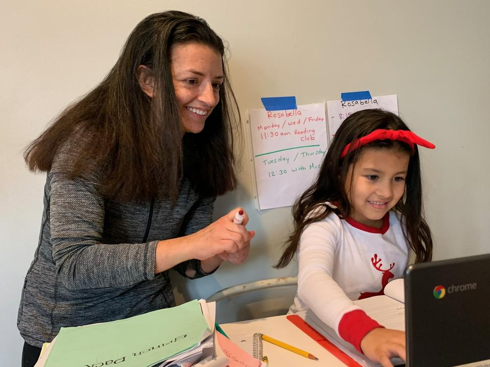 Chantelly Manzanares grades her daughter Rosabella's spelling test.  Because her mother is deaf, Rosabella sometimes uses American Sign Language to interpret what's happening in her classes on Zoom.