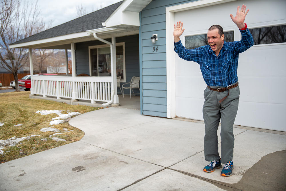 Domier waves to other residents of his group home as they leave the driveway.