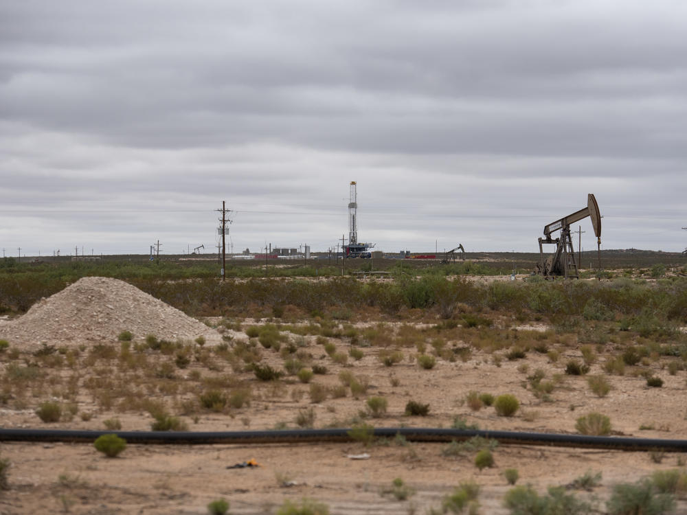 A horizontal drilling rig and a pump jack sit on federal land in Lea County, N.M., in September. The state stands to lose royalties and revenue from a Biden administration pause on new oil and gas leases.