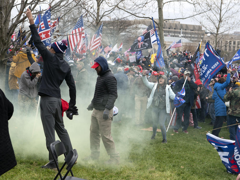 Supporters of former President Donald Trump protest as U.S. Capitol Police officers shoot tear gas outside of the U.S. Capitol on Jan. 6.