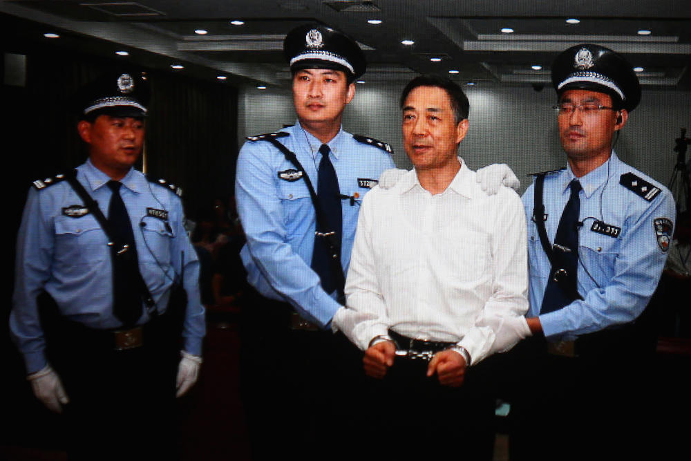 A screen shows the picture of the sentence of Chinese politician Bo Xilai (second right) on Sept. 22, 2013, in Beijing. Bo, who launched an anti-corruption campaign, embezzlement and abuse of power.