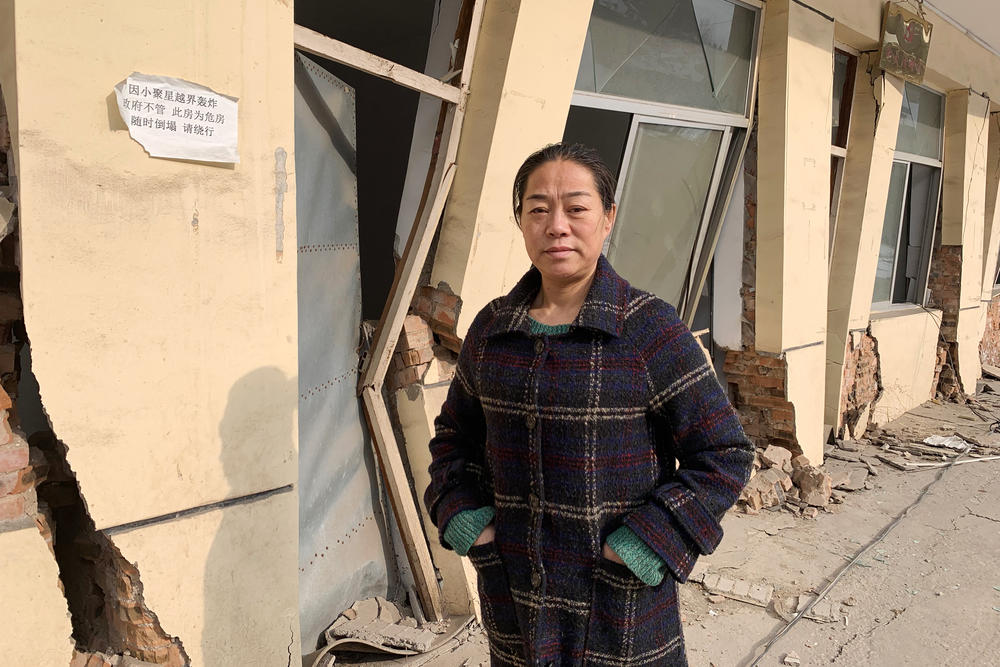 Zhang Xiaohui, the sister of Zhang Zhixiong, in front of Juxin Mining offices. The building and much of the mine collapsed because of tunneling from nearby mines.
