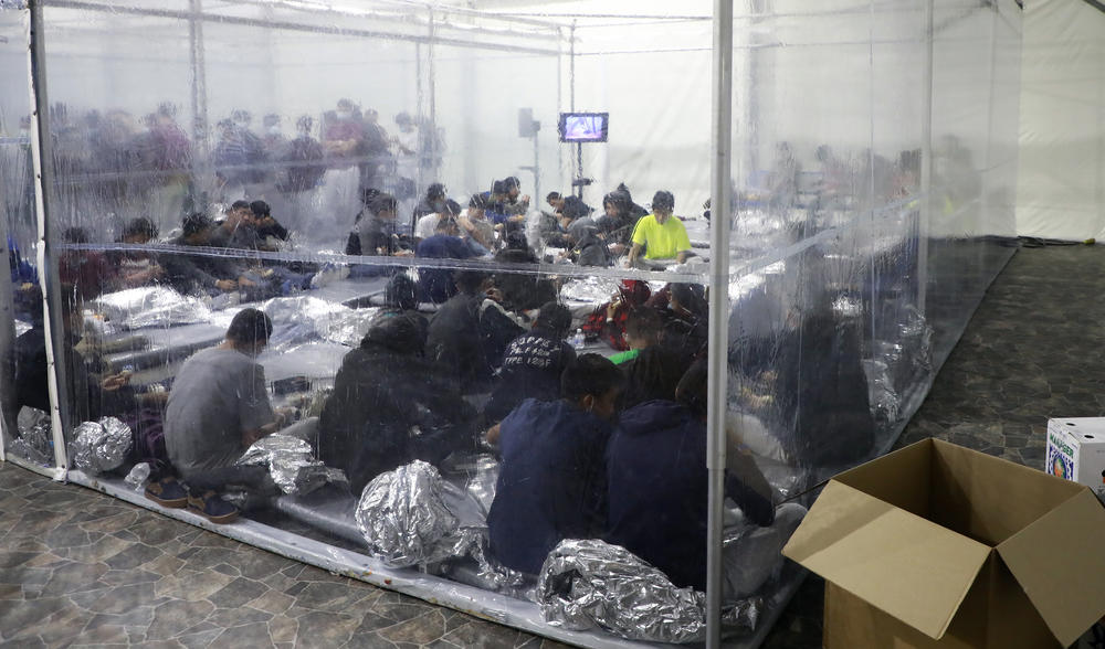 Detained families and unaccompanied children sit in areas divided by plastic sheathing at a temporary processing facility in Donna, Texas.