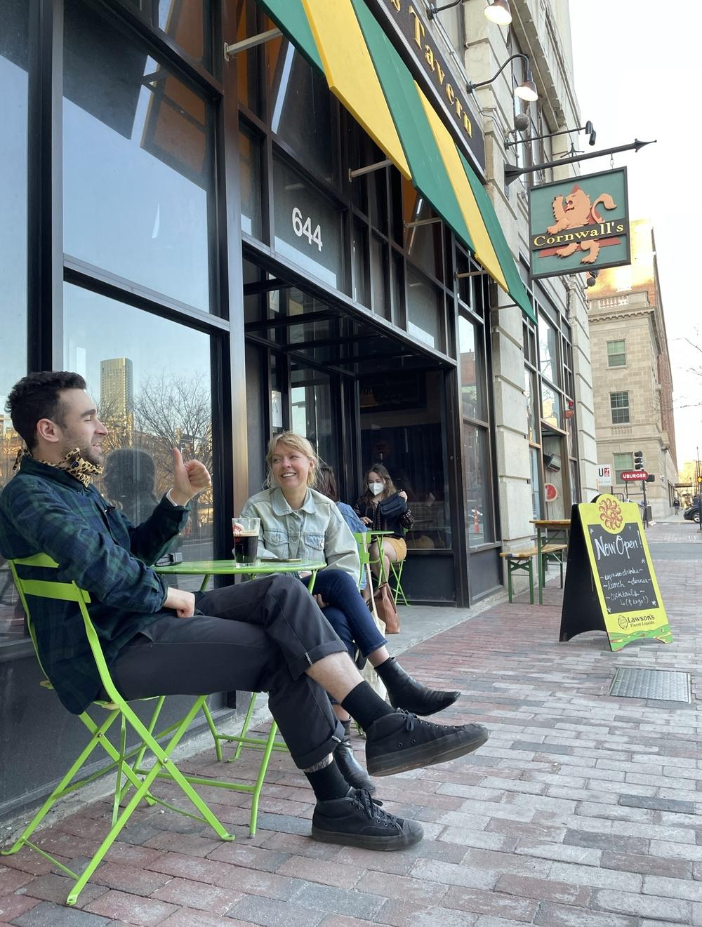 Grad students Julian Geltman and Kailey Slavik savor a cold beer and the warm weather on the first day that Boston restaurants are allowed to put tables out on the sidewalks again, and Cornwall's delights in the extra business.