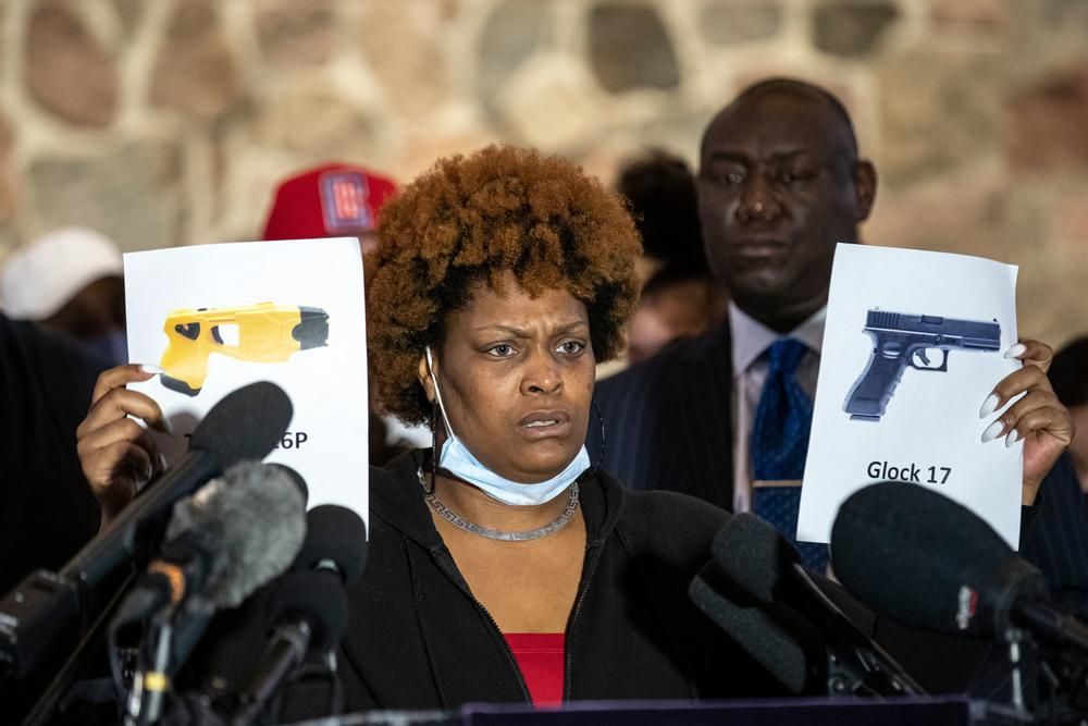Naisha Wright, Daunte Wright's aunt, holds up pictures of a Taser and a handgun Thursday in Minneapolis. She questioned how the ex-police officer charged in her nephew's death could have mixed up the two.
